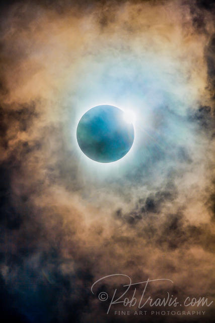Amber solar eclipse with clouds